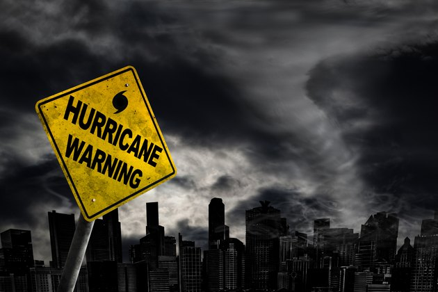Hurricane Warning Sign Against City Silhouette With Copy Space