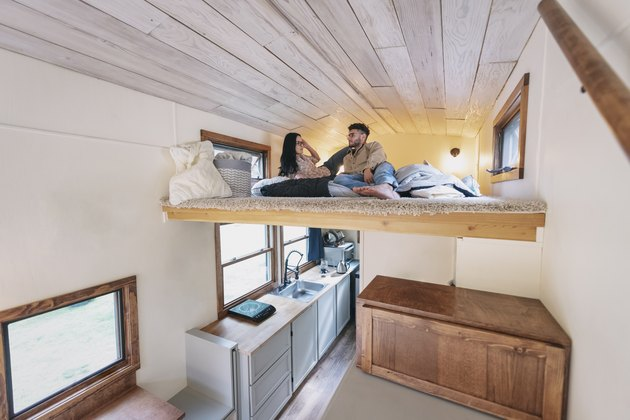 Young couple in bedroom loft of tiny house