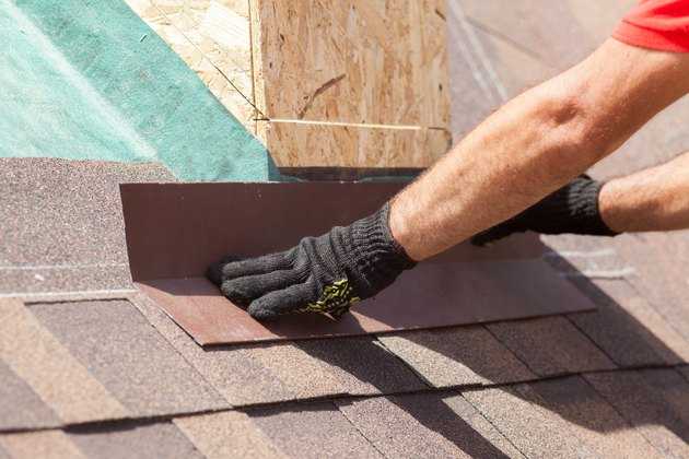 Roofer builder worker installing shingles on a new wooden roof