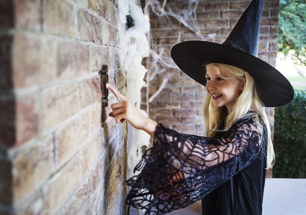 Girl dressed in witch costumes ringing door bell.