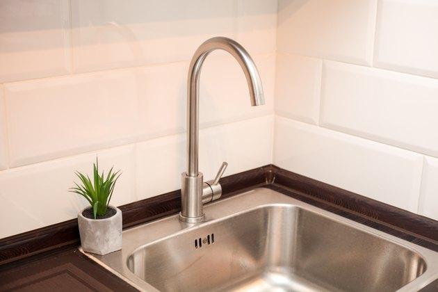 Modern kitchen with metal sink, white decorative wall