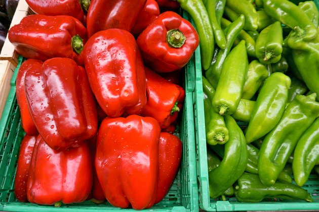 Fresh red bell pepper and green chili in green plastic box, black violet eggplant fruit in wooden box, at the outdoor fresh market