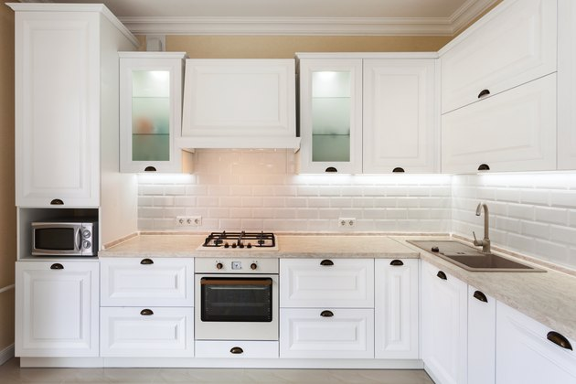 Photo of upscale interior with bright light kitchen cabinet and other designer elements