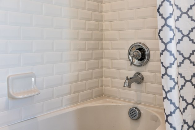 Closeup of modern white shower bath tub with blue curtains in bathroom in model home, apartment or house, tiles, faucet