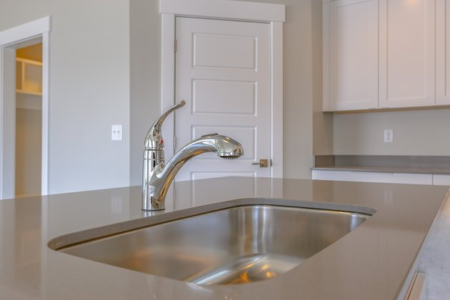Shiny stainless steel sink and faucet on the countertop inside a kitchen