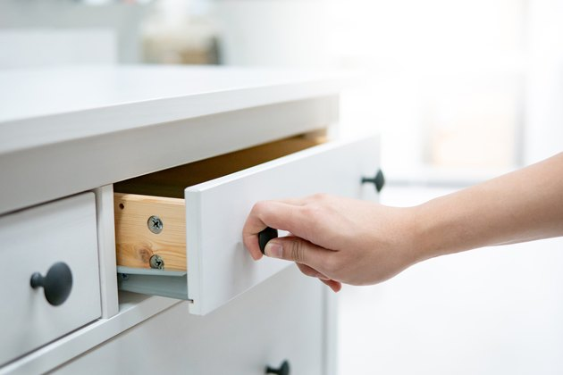 Male hand opening drawer on white cabinet