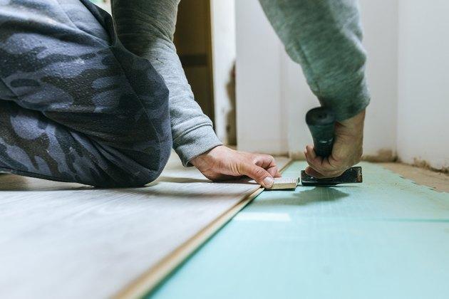 Close-up of man placing parquet floor