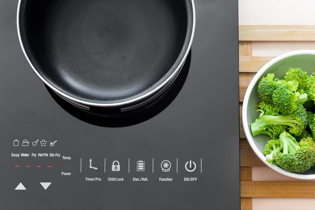 Boiling water at pan on Induction stove top panel for cooking broccoli