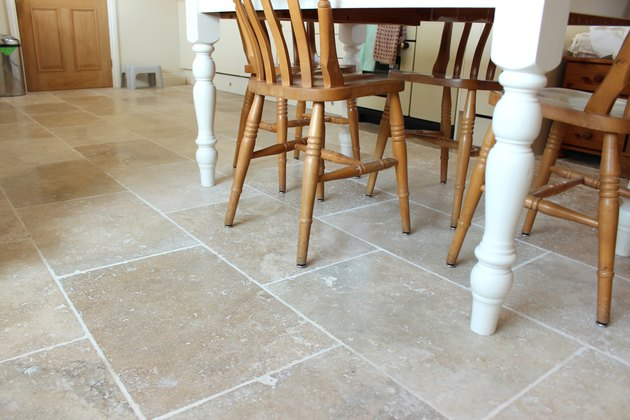 Image of filled travertine tile floor, kitchen table and chairs