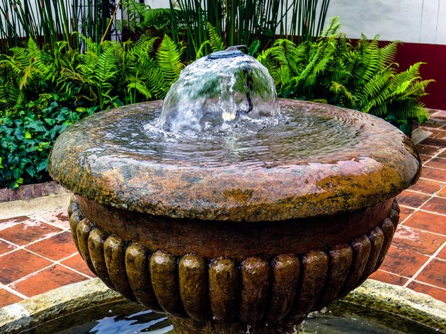 Top of antique water fountain with garden in background