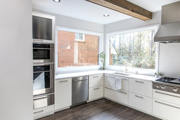 spacious large modern white kitchen recently updated with high end appliances, wood floors, picture windows, white cabinets and wood beams