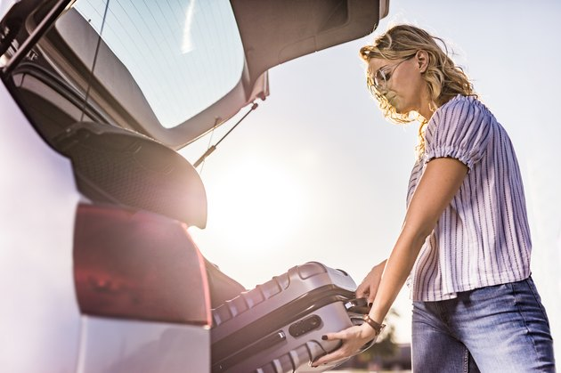 woman loading suitcase in trunk