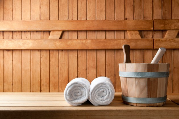 Wooden bucket and white rolled towels in a sauna