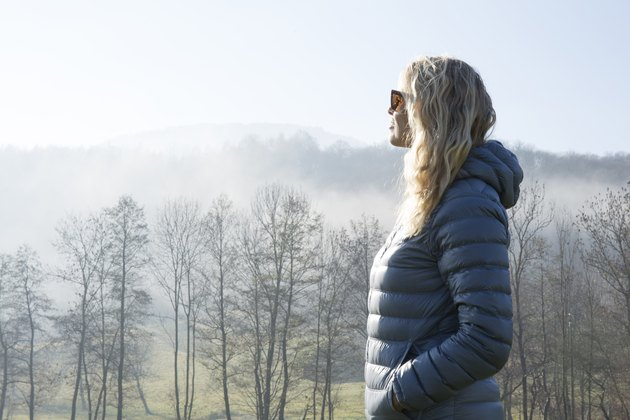 Woman walks through hilly meadow in mist