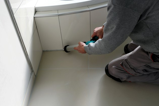 Man sealing a bath or basin with silicone