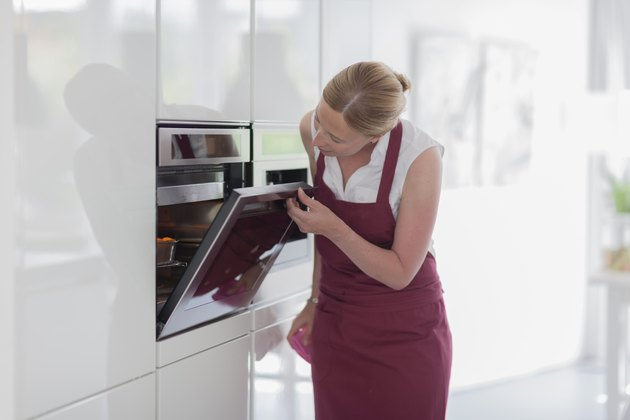 Woman using oven in kitchen