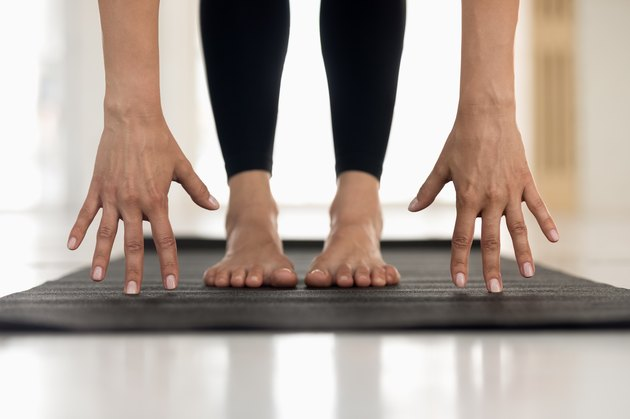 Woman practicing yoga, uttanasana pose, hands and feet close up