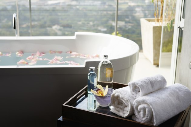 Towels, aromatic oils and orchid next to bathtub