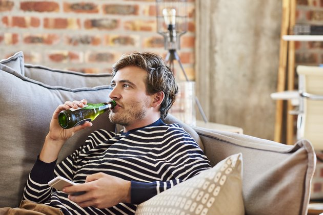 Young man drinking beer while relaxing on sofa