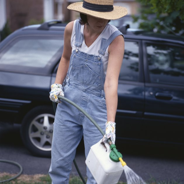 Woman using fertilizer with hose in yard