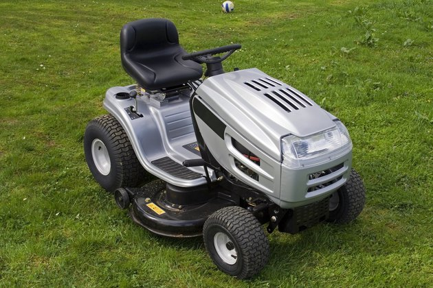 Silver riding lawn mower sitting on lawn