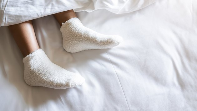 Low Section Of Woman Wearing Sock Relaxing On Bed
