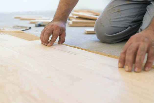 Carpenter lining up parquet-laminate plank