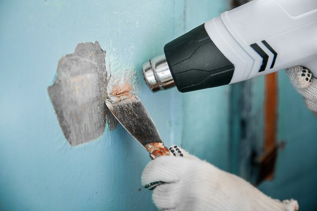 Master removes old paint concrete wall heat gun and scraper
