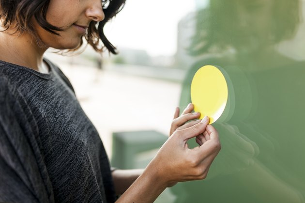 Close-up of woman attaching a sticker on a glass pane