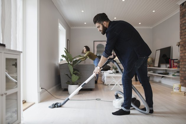 Man vacuuming floor while woman working in living room at home