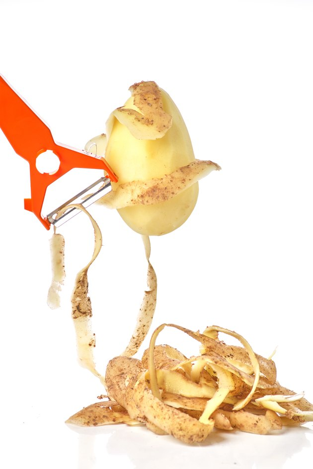 Peeler cleans potatoes, potato skin and peeled potatoes on a white background close-up