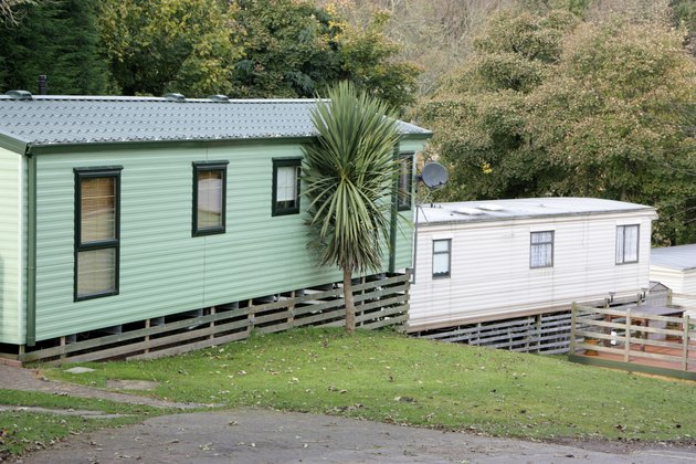 Two mobile homes with wood skirting.