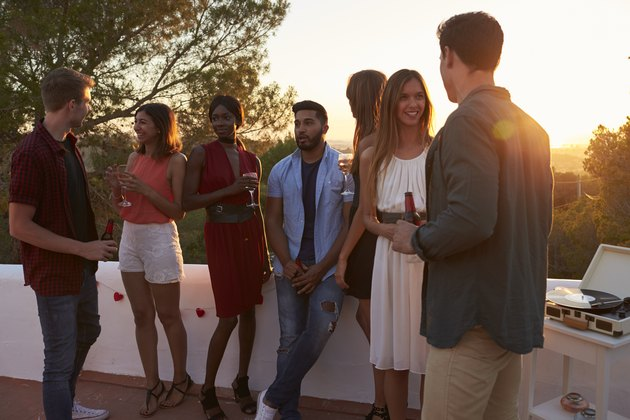 Young adult friends talk at a party on a rooftop at sunset