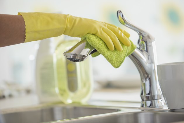 Womans hands in rubber gloves polishing kitchen faucet.