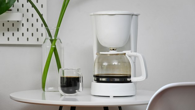 Coffee machine and coffee cup in office room.