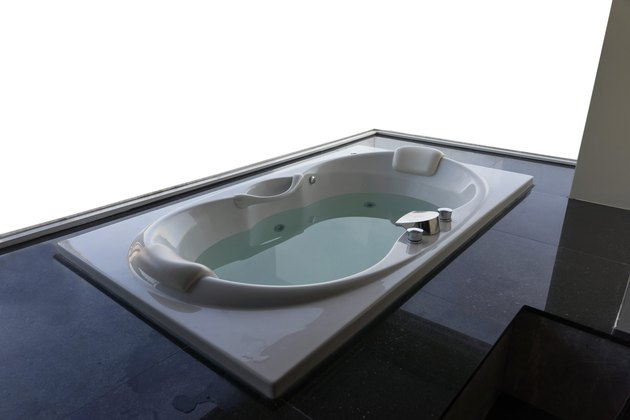 Empty white massaging jetted bathtub with sea and boats background