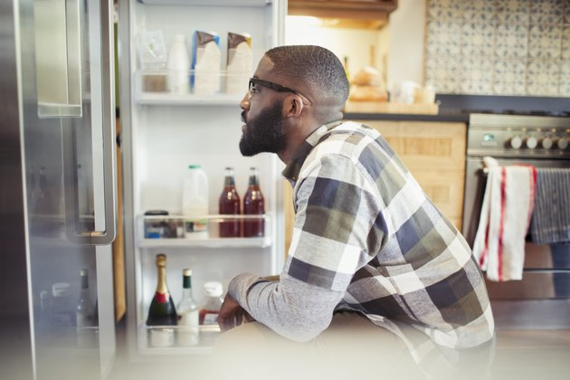 Hungry man peering into refrigerator in kitchen