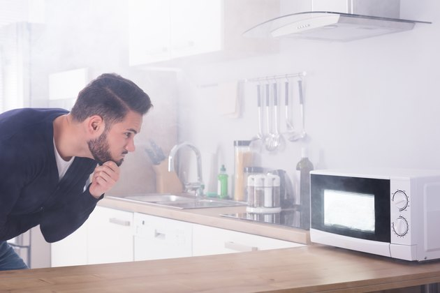 Man Spraying Fire Extinguisher On Microwave Oven