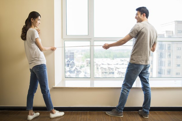 Young couple measuring window