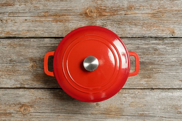 Top view of red enameled iron stockpot on wooden background
