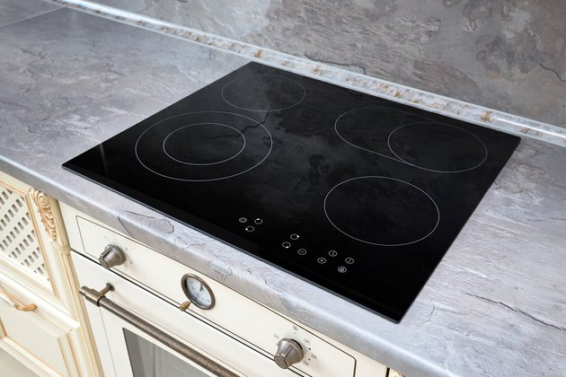 Modern kitchen interior with black induction or electric hob stove cooker with ceramic top surface with marble countertop and wall decorated with stone.