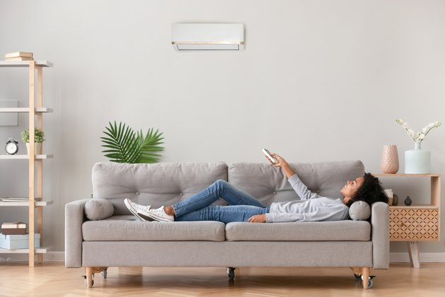 African female lying on couch use airconditioner breathing fresh air