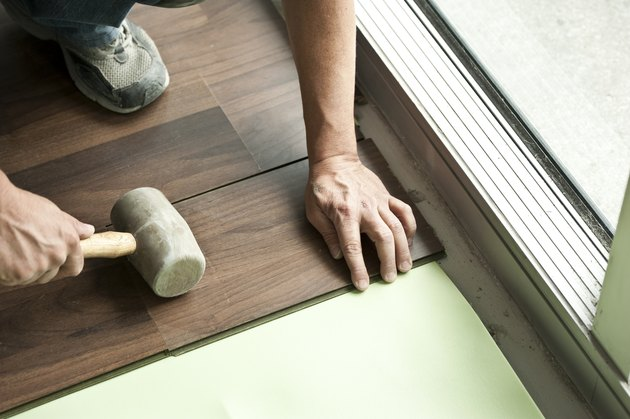 Two male hands holding mallet installing hardwood floor.