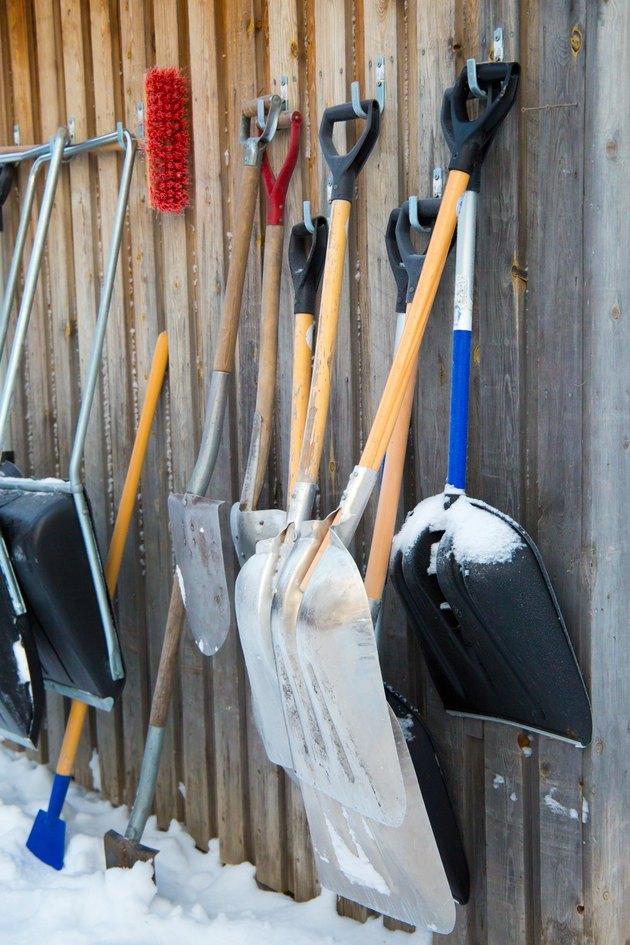 Snow shovels hanging against barn.