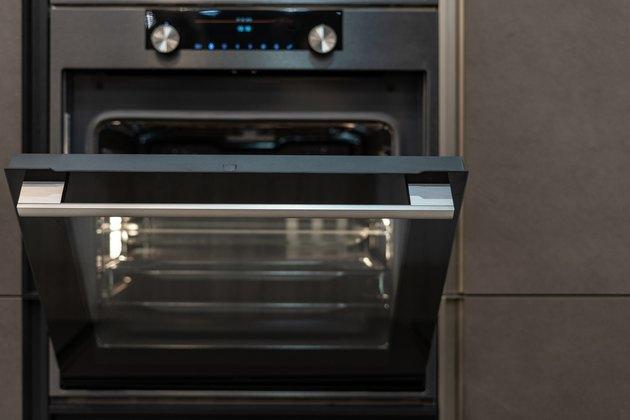 Front view photo of open door on  modern oven built-in in black kitchen cabinet