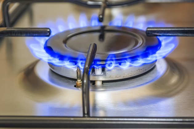 Close-up view of a kitchen cooker with blue flame