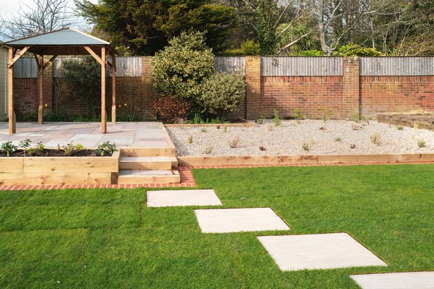 New stepping stones leading to steps and a raised patio with a wooden gazebo, next to a gravel stone planting area. The new turf has a brick mowing strip.