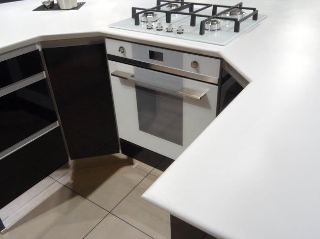 Modern monochrome, black / white kitchen, gas-hob, electric-oven, corian worktop-counter, island