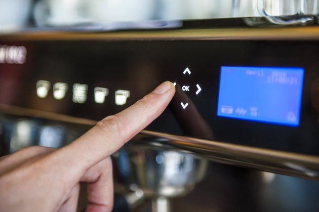 Finger pushing digital button on coffee machine