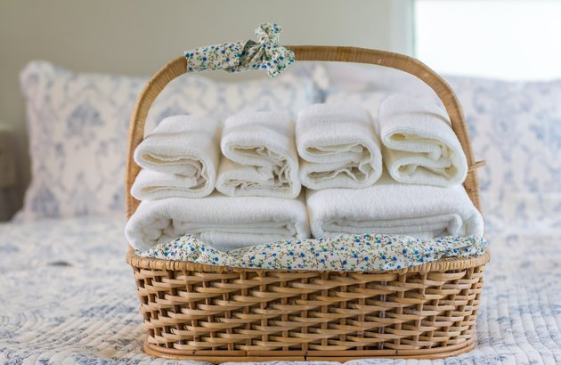 Close-Up Of Towels In Wicker Basket On Bed At Home